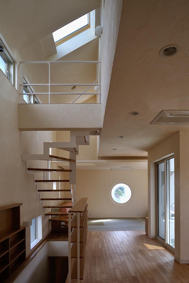 恵比寿N邸8-キッチンから丸窓のあるリビングとダイニングを見る
